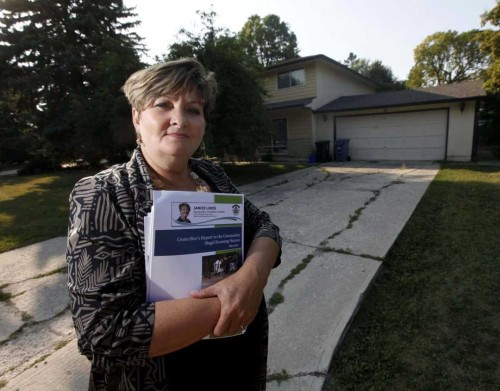 PHIL HOSSACK / WINNIPEG FREE PRESS  -  City Counsilor Janice Lukes stands in front of a Thatcher Drive house used as an illegal rooming house Wednesday evening. She's holding a report to be released Thursday on the issue.  See story - August 30, 2017
