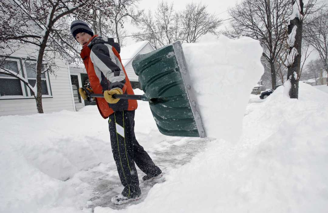 Mike Flynn shovels snow Tuesday, March 5, 2013, in Minneapolis as a winter storm dumped snow on much of the state. Tens of thousands of Minnesota students got a day off Tuesday as the second day of a slow-moving snowstorm made travel difficult across much of the region. (AP Photo/Jim Mone)